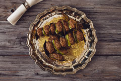 Mince meatball on a spit. (Italian dish) surrounded by glass, dishes and cuttlery, an elegant napkin on the table. everything on a gray wooden table with a gray royalty free stock photos