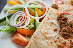 A mince pancake with salad on the side. Fresh beef mince pancake with fresh green salad on the side Royalty Free Stock Images