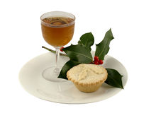A Mince Pie and Sherry. A Christmas mince pie with a glass of sherry and a sprig of holly stock image