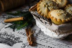 Mince pie w koszu na stole z rocznika bieliźnianym płótnem z gazetowym drukiem, cynamonowymi kijami i jedlinowymi gałąź, boże nar fotografia stock