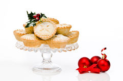 Mince Pies. Freshly baked Christmas mince pies on glass comport with red bauble decorations Royalty Free Stock Photography