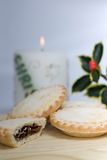 Mince pies, holly and a burning candle Royalty Free Stock Image