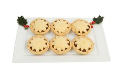 Mince pies with holly. Mince pies decorated with stars on a rectangular plate with holly isolated, against white Royalty Free Stock Image