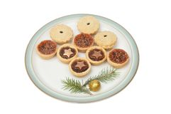 Mince pies on a plate. Festive mince pies on a plate decorated with pine needles and a gold bauble isolated against white stock photo
