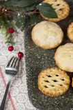 Mince pies on a tray with festive christmas decorations. Selection of fresh frosted mince pies on a tray with festive christmas decorations on a country table Stock Photos