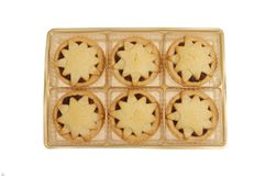 Mince pis in a tray. Star decorated mince pies in a gold colored plastic tray isolated against white Stock Photos