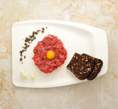 Minced beef with raw egg on a white Board Royalty Free Stock Photo