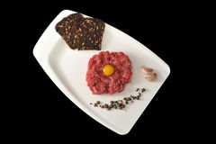 Minced beef with raw egg on a white Board tray on black backgrou Royalty Free Stock Photo
