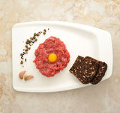 Minced beef with raw egg on a white Board tray Stock Images