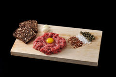 Minced beef with raw egg on a wooden Board on black background Stock Images