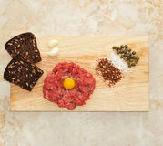 Minced beef with raw egg on a wooden Board. With slices of bread, garlic, capers, salt and spices. top view Stock Photography