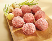 Minced delicatessen meat on a cutting board. Raw delicatessen minced meat on a cutting board and vegetables royalty free stock photography