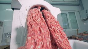 Minced meat is being extruded from a mincing machine. 4K stock video footage