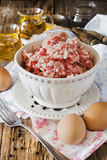 Minced meat in a bowl. And different ingredients on an old wooden table. meat dishes Stock Photo