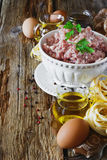 Minced meat in a bowl. And the ingredients for making pasta dishes on the old wooden table. european cuisine Royalty Free Stock Photos