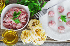 Minced meat. In a bowl and the ingredients for making pasta dishes on the old wooden table. european cuisine Royalty Free Stock Photos