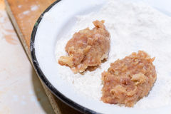 Minced meat burgers poaching in the flours.  Royalty Free Stock Images