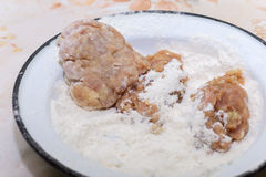 Minced meat burgers poaching in the flours.  Stock Photo