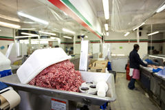 Minced meat in container with employee standing in background at store Stock Photo