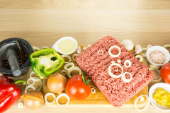 Minced meat on cutting board, pounder and vegetables on wooden b. Ackground, top view Stock Photos