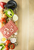 Minced meat on cutting board, pounder and vegetables on wooden b. Ackground, top view, room for text Stock Image