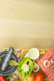 Minced meat on cutting board, pounder and vegetables on wooden b. Ackground, top view, room for text Stock Images