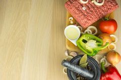 Minced meat on cutting board, pounder and vegetables on wooden b. Ackground, top view, room for text Stock Photography