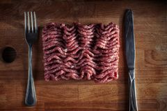 Minced meat on a cutting board. Meat stuffing with a fork and knife. on a cutting board. View from above Stock Photography