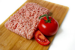Minced meat on a cutting board with tomato Stock Photo