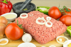 Minced meat on cutting board and vegetables on wooden background. Minced meat on wooden cutting board and vegetables on wooden background Royalty Free Stock Photos