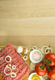 Minced meat on cutting board and vegetables on wooden background. Top view, room for text Royalty Free Stock Photography