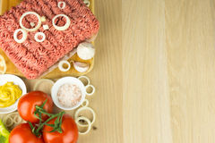 Minced meat on cutting board and vegetables on wooden background. Top view, room for text Royalty Free Stock Photos