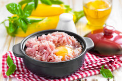 Minced meat with egg. In a bowl on a table Stock Image