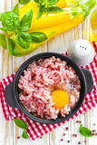 Minced meat with egg. In a bowl on a table Stock Photography
