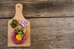 Minced meat with egg yolk, onions and olives on wooden tray. Against wooden background Royalty Free Stock Image