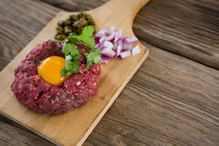 Minced meat with egg yolk, onions and olives on wooden tray. Against wooden background Royalty Free Stock Photography
