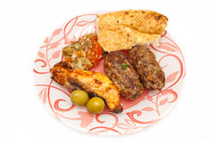 Minced meat and fish kebab. Served with bread and fresh salad Stock Photography