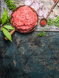 Minced meat in frying pan with wooden cooking spoon and fresh flavoring on rustic background, top view. Place for text stock photo
