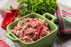Minced meat. In green bowl on white table with seasoning. Selective focus Stock Photo