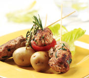 Minced meat kebabs and new potatoes. Minced meat kebabs on sticks and new potatoes Royalty Free Stock Photos