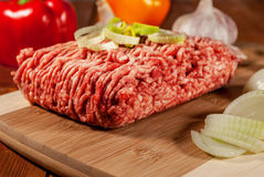Minced meat. Mincet meat with vegetables on wood plate Royalty Free Stock Photos