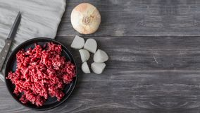 Minced meat, raw red beef. onion, garlic cloves on wooden table. Copy space Royalty Free Stock Image