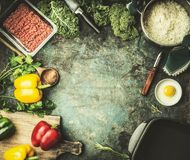 Minced meat with rice, kale and vegetables ingredients on kitchen table background, top view. Frame Royalty Free Stock Images