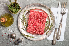 Minced meat with seasoning and fresh thyme. Minced meat on metal plate with seasoning and fresh thyme on gray background, top view Stock Images