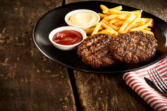 Minced meat stakes with french-fries. Minced meat stakes with french fries and sauces served on old wooden table surface with napkin Stock Image