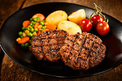 Minced meat steaks. With potato and vegetables served on black dish with cherry tomatoes stock photo