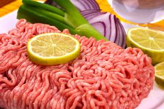 Minced Meat. Minced uncooked meat on white plate with vegetable Stock Images
