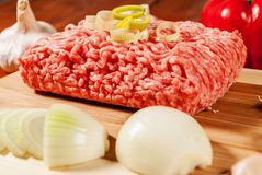 Minced meat. With vegetables on wood plate Stock Photos