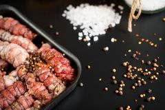 minced meat wrapped in rolls lies in a frying pan standing on a black background stock photography