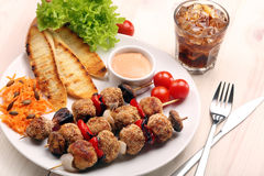 Minced meatballs baked as skewers with carrot salad Stock Images